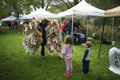 Two kids listen to Sue Anderson as she explains about plastic waste. Anderson wore the costume to promote Plastic Free MKE at the Fish and Feather Festival.