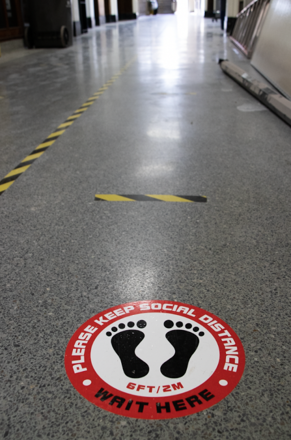 Marking on the high school floor direct traffic. If school were to resume some in-person learning, hallway traffic would likely be highly regulated.