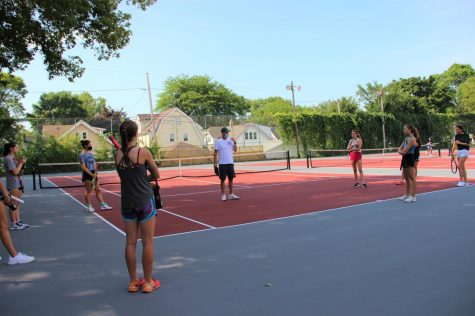 The girls tennis team stands spaced out as they listen to their coach. Their season will continue, but with masks, social distancing and individual tennis balls.