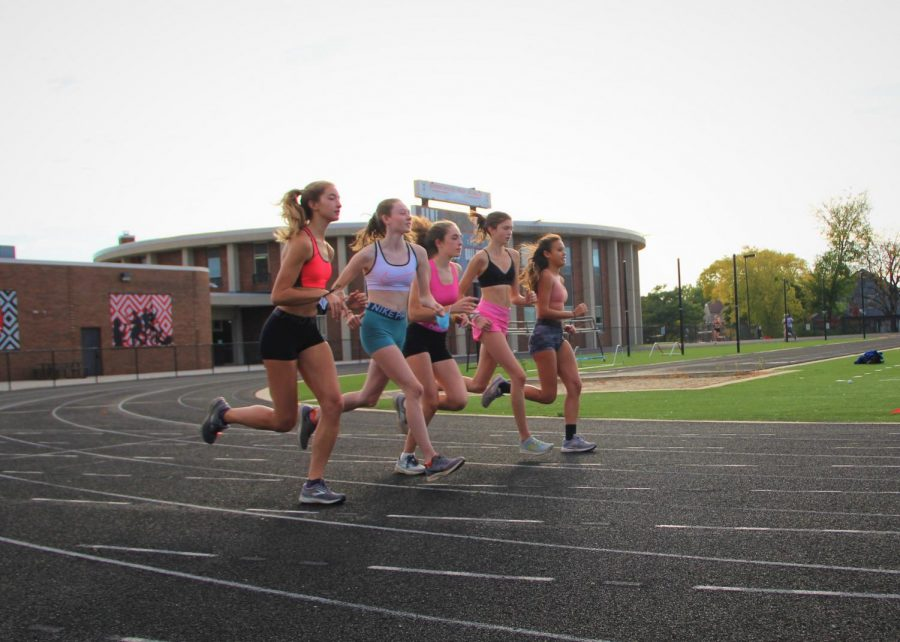 Isabella Lozier and Annika Elliott, juniors, Louisa Fowler, sophomore, Addie Kemp, senior, and Grace Optekar, junior, run on the track at practice. The team hopes to make it to D1 state.