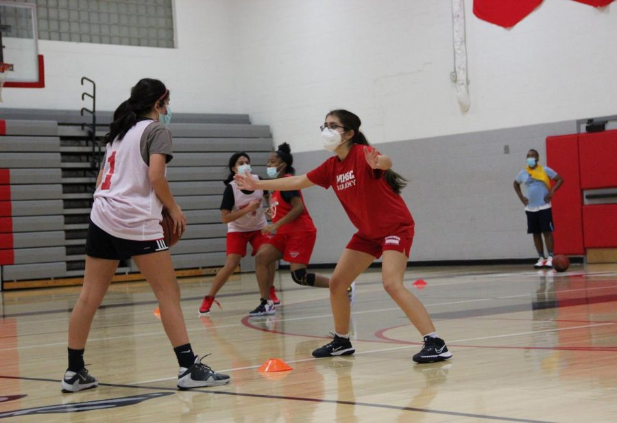 Nayana Menon, in white, holds the ball, while Sonia Bendre, in red, defends. In the back, Neveah Gomez, in white, goes up against Brooklyn Anderson, in red.