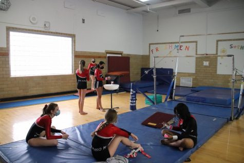 Members sit on the mat relaxing, as their teammates prepare to attempt a skill. The coaches hope the girls complete skills they have been working on.