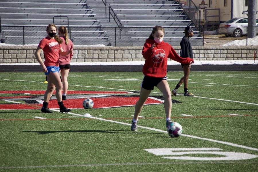 Lucy Corcoran, senior, dribbles the ball as Fiona Skwierawski, junior, watches. Girls soccer, like track, will use its 15 contact days to get a headstart on the season.