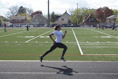 Delea Martins in mid-sprint along the track. Martins has set school records in the 200-meter dash and 400-meter dash. She hopes to set state records.