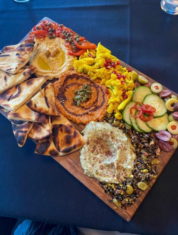 The Mezze Platter served on a wooden cutting board features three different dips, pickled vegetables and pita bread.